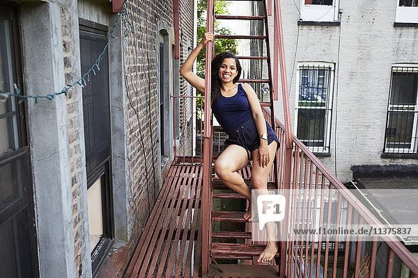 Portrait of smiling woman sitting on urban fire escape