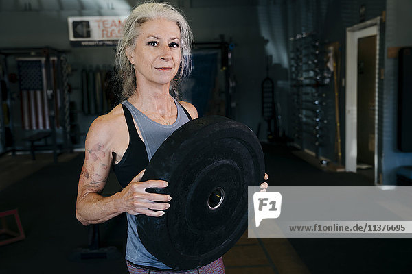 Caucasian woman holding large weight in gymnasium