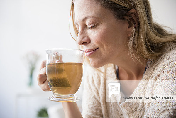 Caucasian woman smelling cup of tea