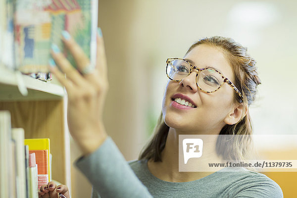Mixed Race girl choosing book in library