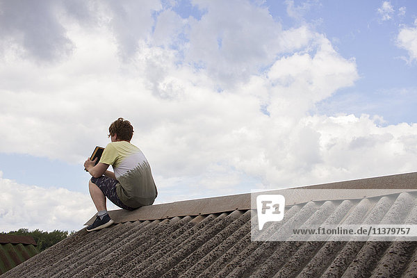 Caucasian man sitting on roof holding book