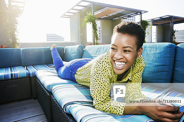 Black woman laying on rooftop sofa laughing