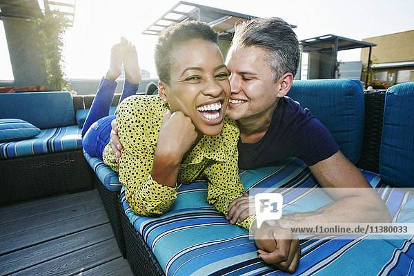 Couple cuddling on rooftop sofa