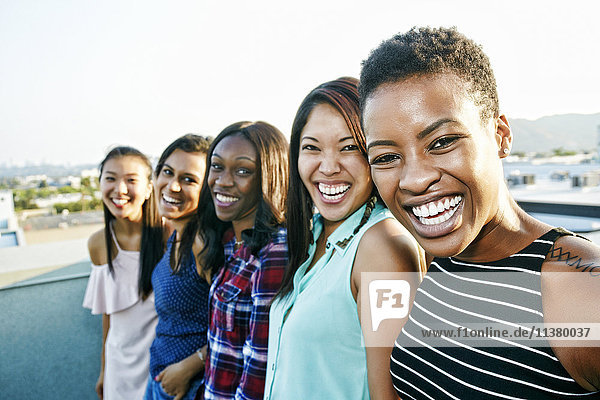 Smiling women standing in a row on rooftop