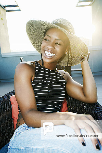 Black woman wearing sun hat on rooftop