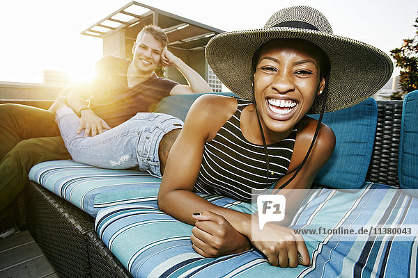 Portrait of smiling couple on rooftop sofa