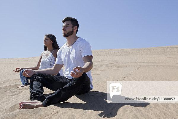 Hispanic couple meditating at beach