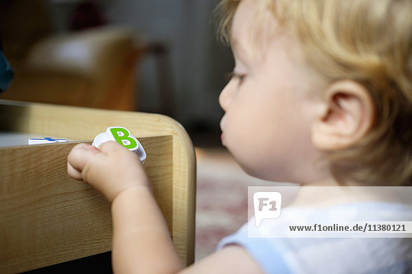 Caucasian baby boy holding toy letter