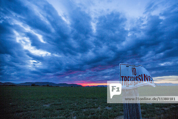 No trespassing sign under clouds at sunset