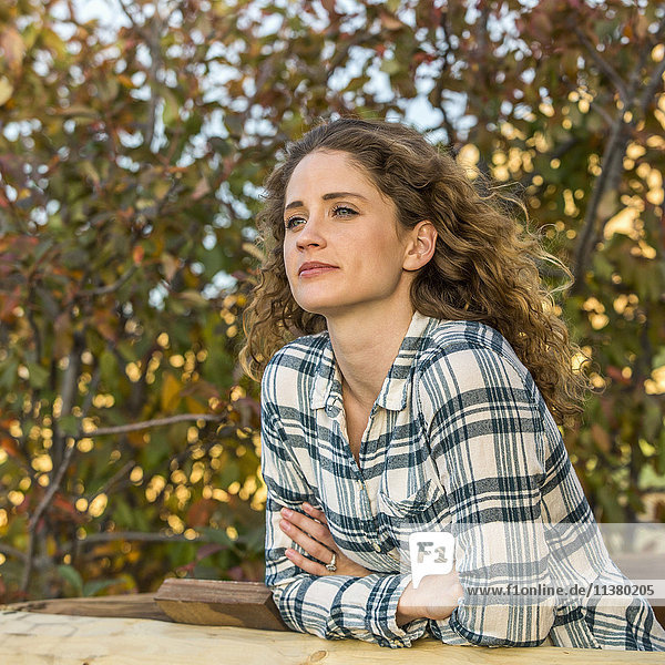 Caucasian woman leaning on wooden fence