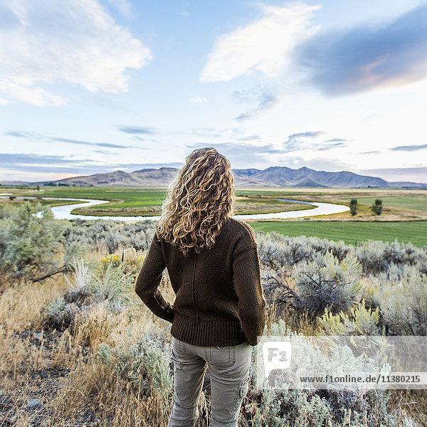 Caucasian woman standing near winding river