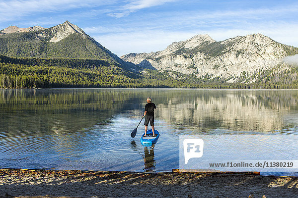 Caucasian man paddleboarding on mountain lake