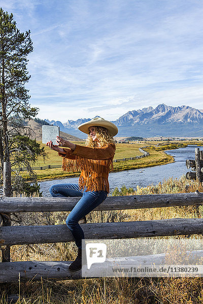 Caucasian woman sitting on wooden fence posing for selfie