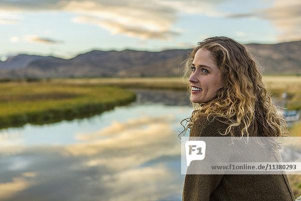 Caucasian woman smiling near mountain river
