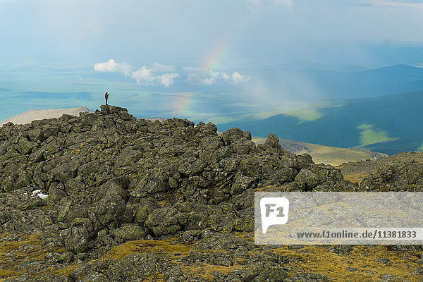 Man standing on rock formation looking at rainbow