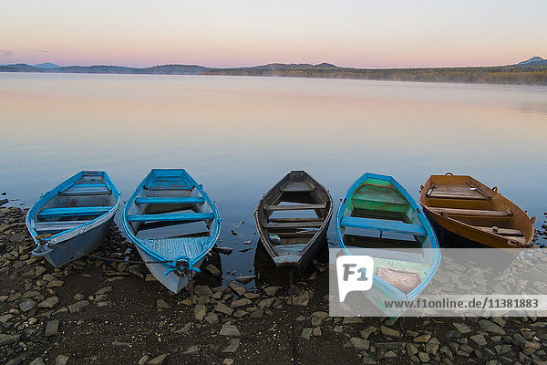 Five empty rowboats on rocky shore of lake at sunset