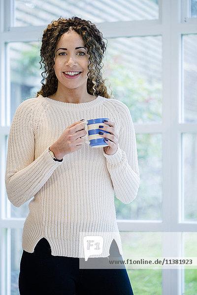 Woman standing near window holding coffee cup
