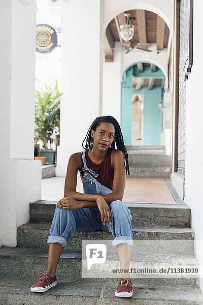Serious Mixed Race woman sitting on staircase