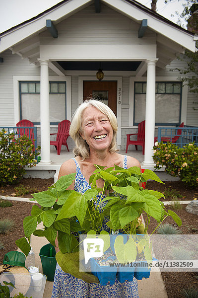 Portrait of smiling Caucasian woman holding tray of plants near house