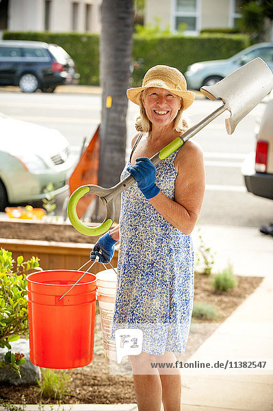 Portrait of smiling Caucasian woman holding shovel and buckets