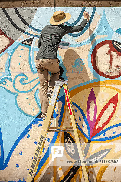 Man standing on ladder painting mural on wall