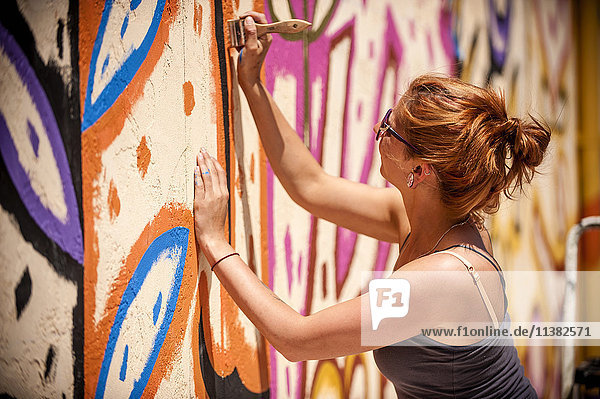 Caucasian woman painting mural on wall