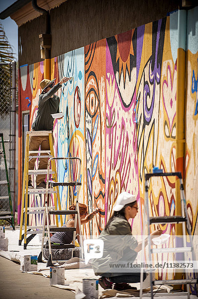 People painting mural on wall
