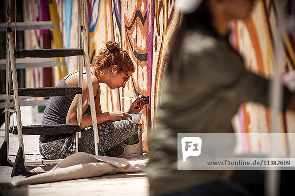 Women sitting on tarp painting mural on wall