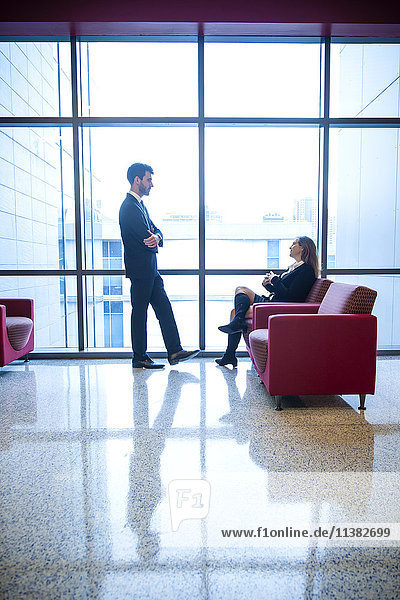 Businessman and businesswoman talking in office lounge