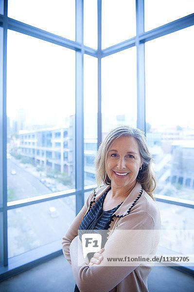 Portrait of smiling Caucasian businesswoman posing near window