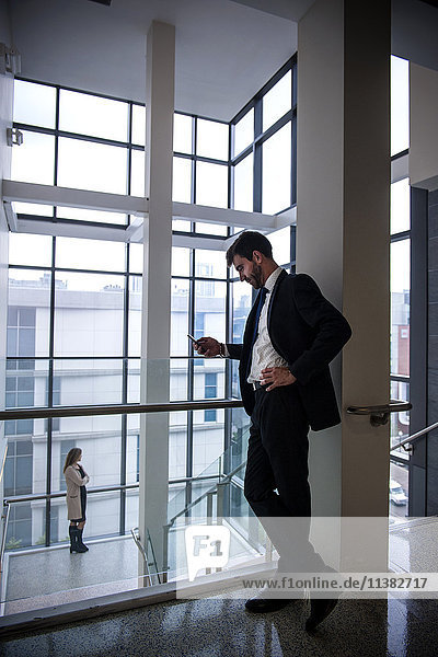 Businessman texting on cell phone near staircase