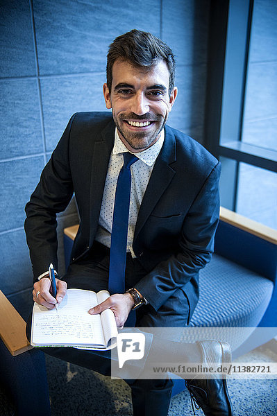 Smiling Hispanic businessman writing on notepad in office lounge