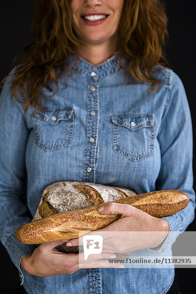 Smiling Caucasian woman holding bread