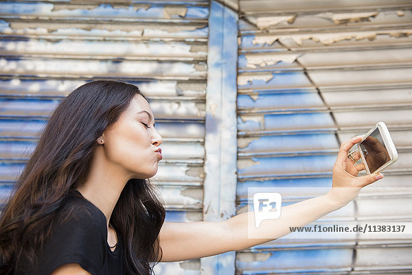 Thai woman puckering for cell phone selfie