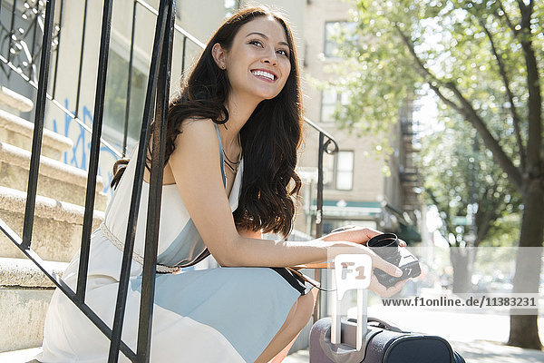 Thai woman sitting on urban staircase with camera and suitcase
