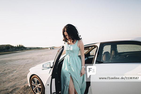 Caucasian woman standing near open car door