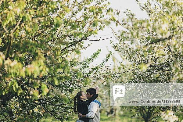 Caucasian couple kissing near trees