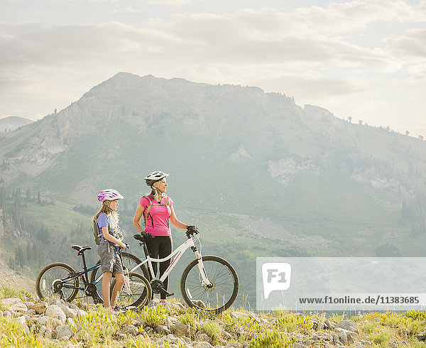 Caucasian grandmother and granddaughter standing with mountain bikes