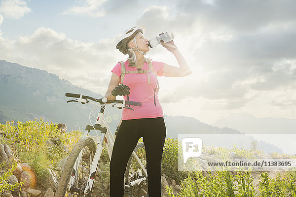 Caucasian woman with mountain bike drinking from bottle