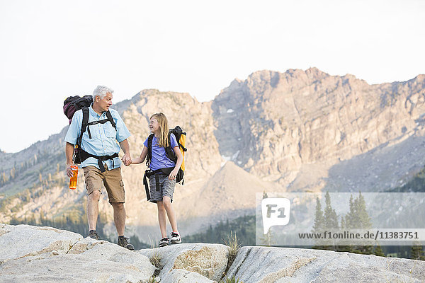Caucasian grandfather and granddaughter hiking on mountain