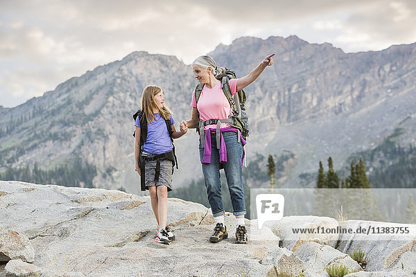 Caucasian grandmother and granddaughter hiking on mountain