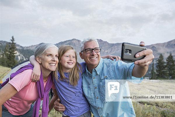 Caucasian grandparents and granddaughter posing for cell phone selfie
