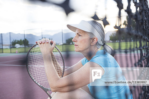 Caucasian woman resting and holding tennis racket