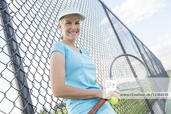 Caucasian woman holding tennis racket leaning on fence