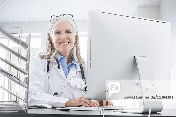 Smiling Caucasian doctor using computer at desk