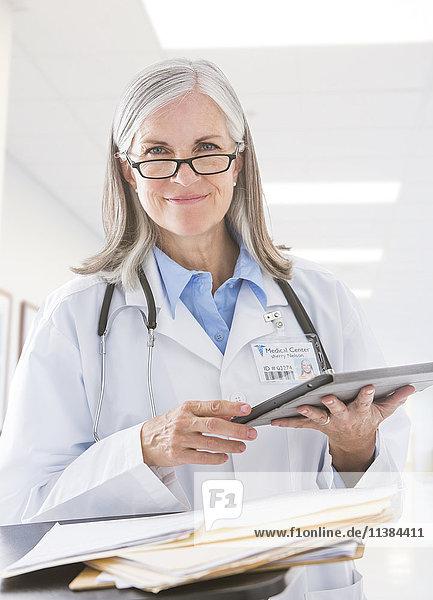 Caucasian doctor holding digital tablet in hospital