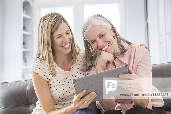 Smiling Caucasian women using digital tablet