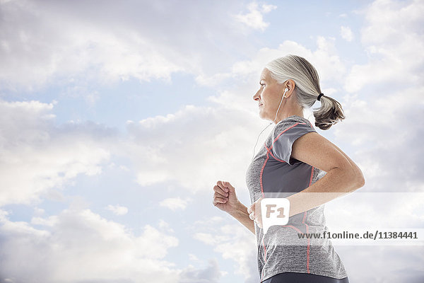 Caucasian women wearing earbuds running against clouds