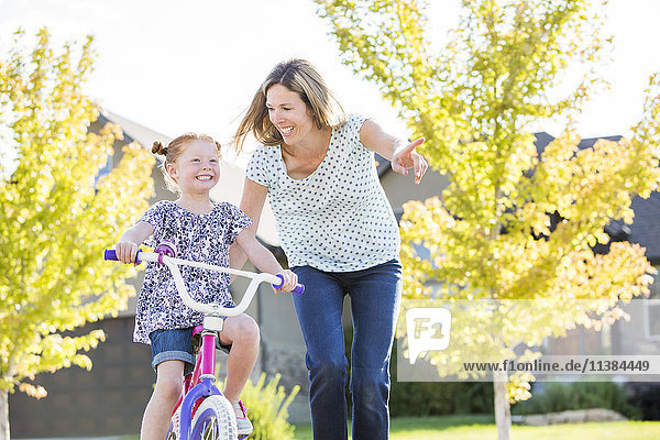 Caucasian mother teaching daughter to ride bicycle