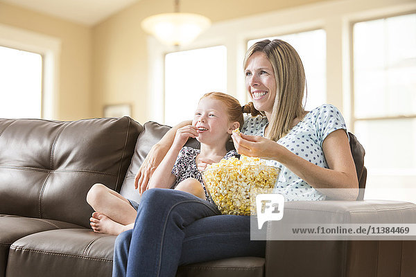 Caucasian mother and daughter sitting on sofa eating bowl of popcorn
